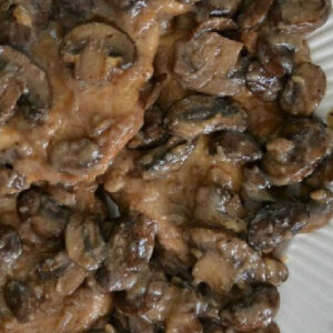 closeup of chicken marsala topped with mushrooms