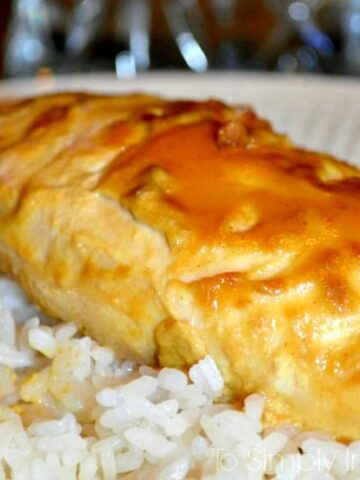 A close up of a chicken breast topped with maple dijon sauce over white rice