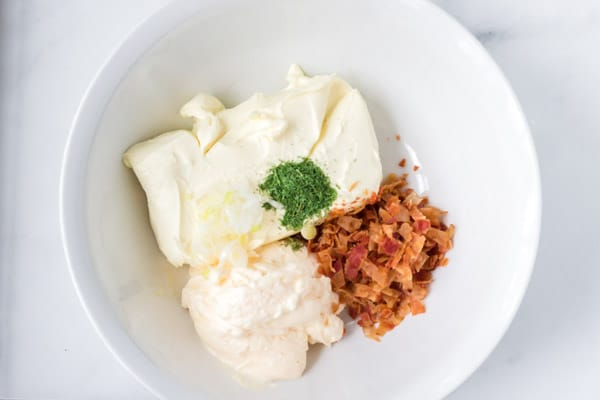 white bowl with cream cheese, bacon crumbles, mayo, and dill