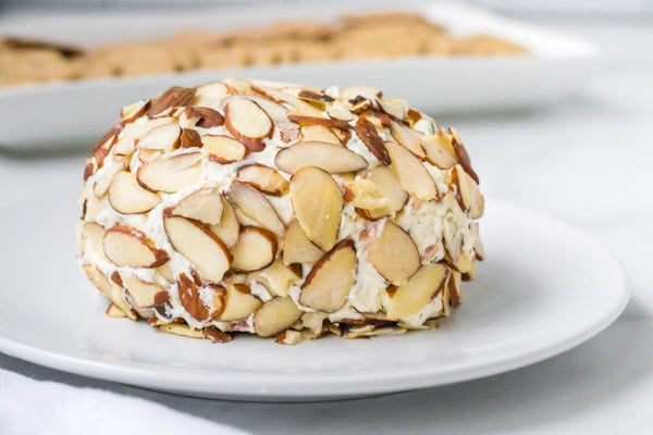 almond coated bacon cheese ball on a white plate