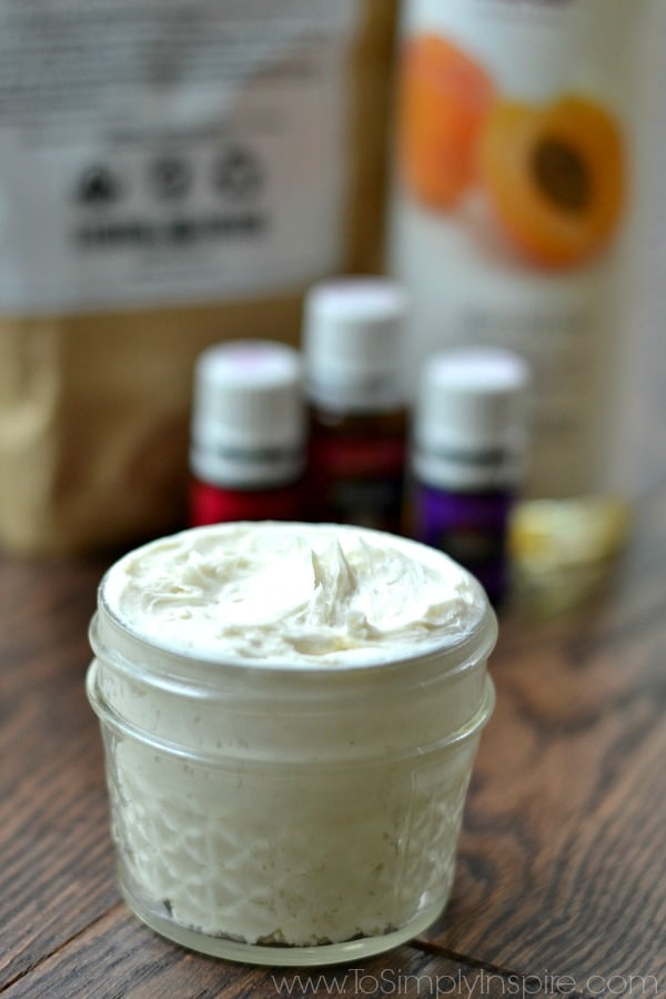 A close up of homemade lotion in a mason jar with essential oil and apricot oil