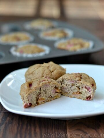 a plate with two banana rhubarb muffins with a muffin tin in the background