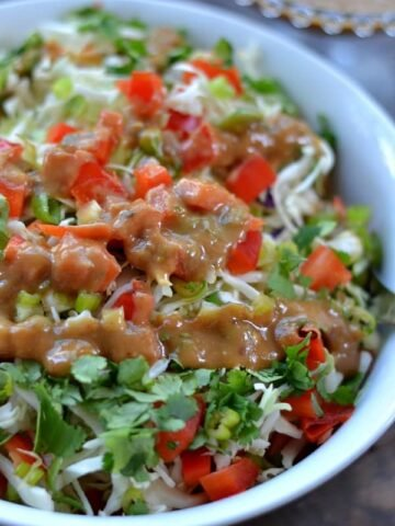 A close up of a bowl of lettuce with diced red peppers and a Thai peanut butter dressing drizzled on top