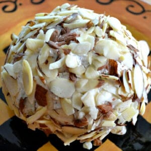 almond covered bacon dill cheeseball on a brown plate