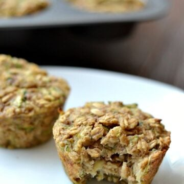 a closeup of 3 oatmeal zucchini muffins on a white plate