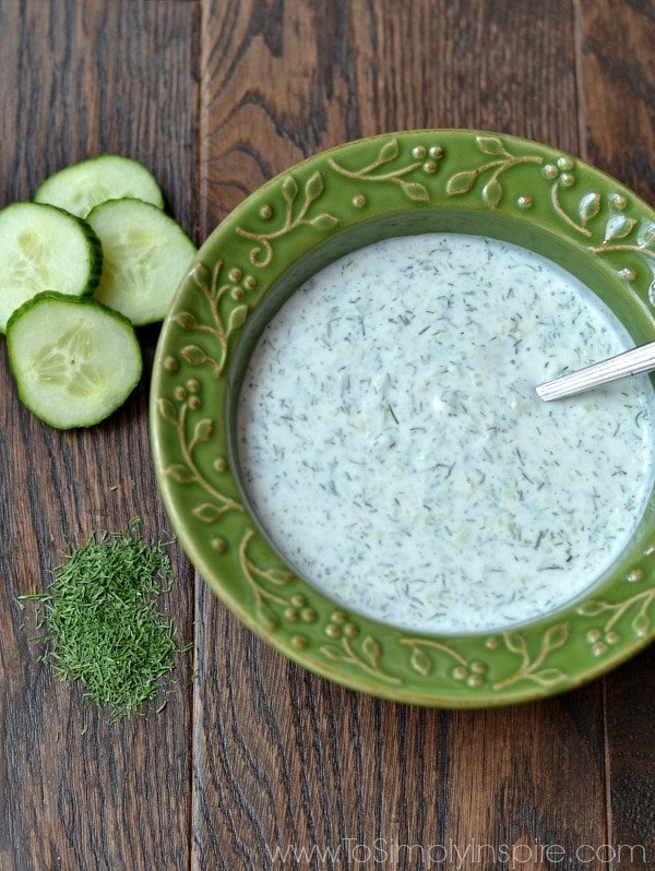 A green bowl of Cucumber Dill sauce on a wood table