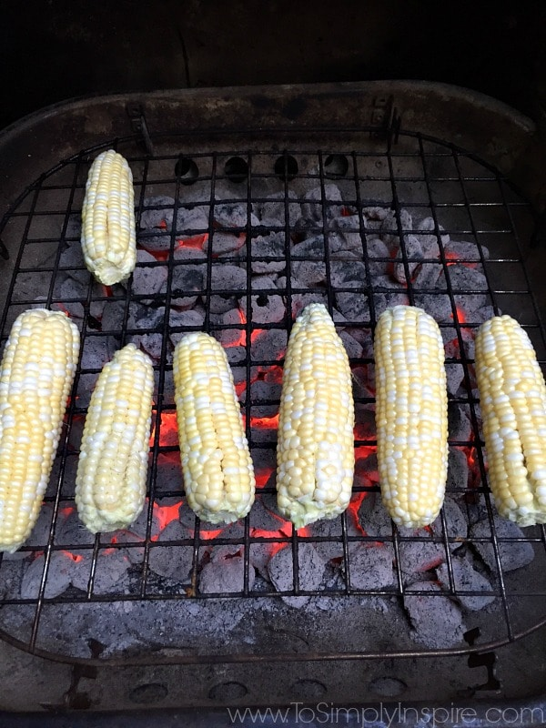 seven ears of corn cooking on a grill