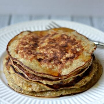 A stack of Banana Pancakes on a white plate covered in syrup