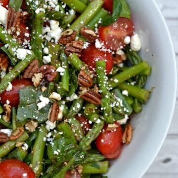 A bowl of salad with spinach asparagus and tomatoes with pecans and feta cheese
