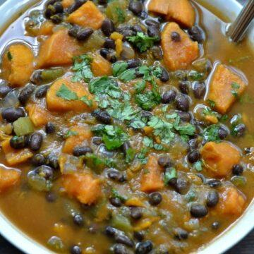 A bowl of sweet potato black bean soup in a white bowl