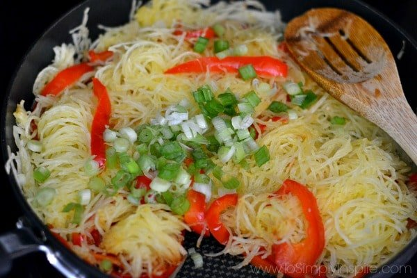 A pan filled with Spaghetti squash, red pepper slices and green onions
