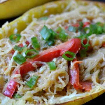A close up of a spaghetti squash with red pepper slices and scallions