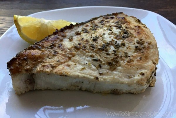 closeup of swordfish steak on a white plate with a lemon wedge