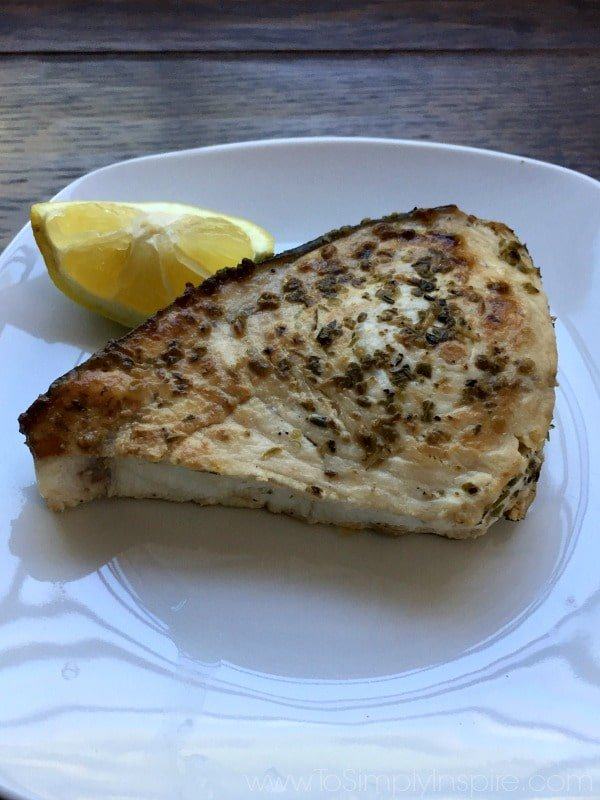 A piece of Swordfish on a white plate with a lemon wedge