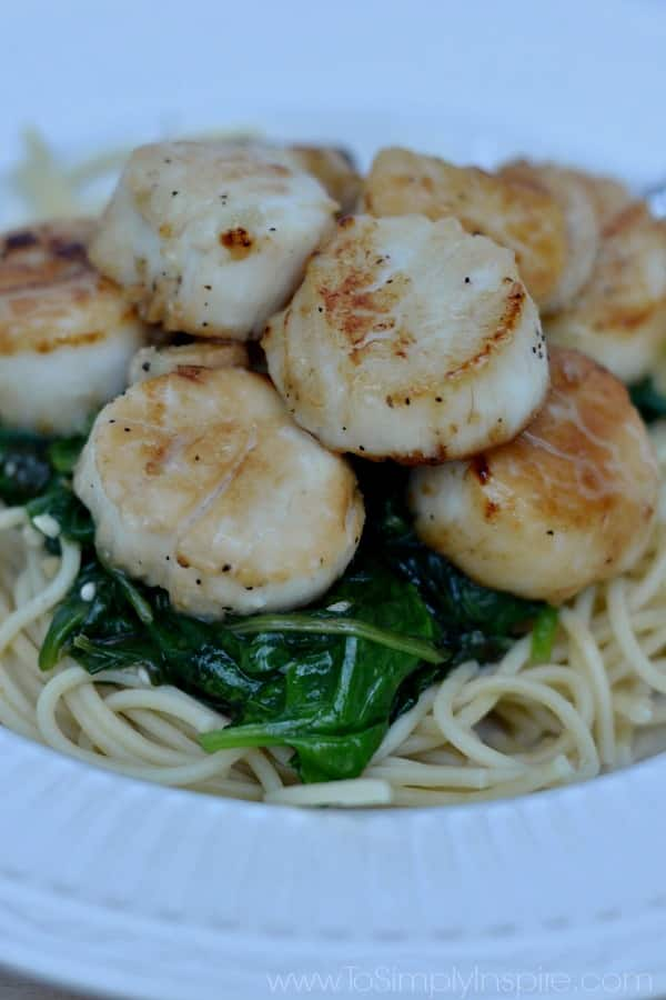Sauteed Scallops Recipe over spinach in a white bowl