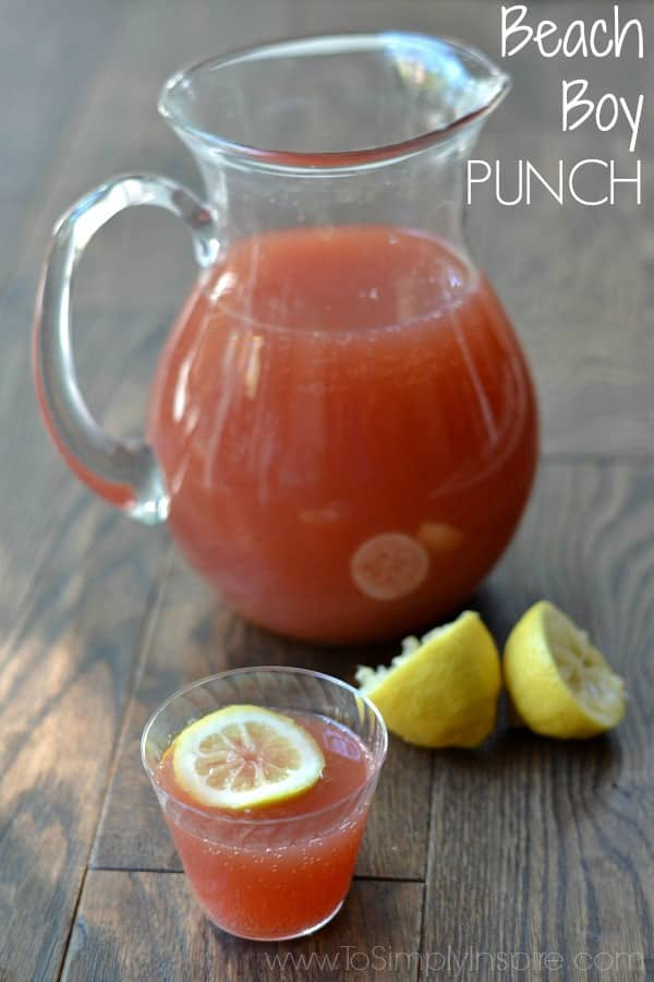 A pitcher of red punch with a cup in front