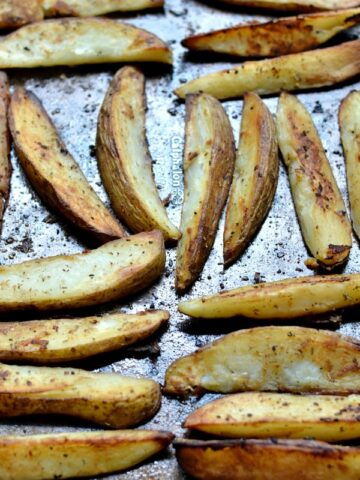 a baking sheet full of potato wedges