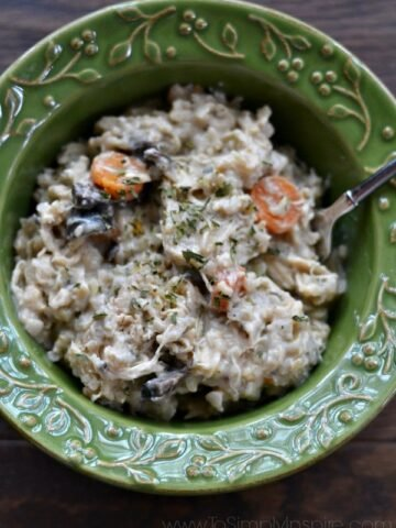 A green bowl of creamy chicken and brown rice casserole with a spoon