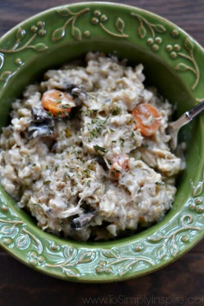 green bowl full of chicken and rice casserole with carrots and mushrooms