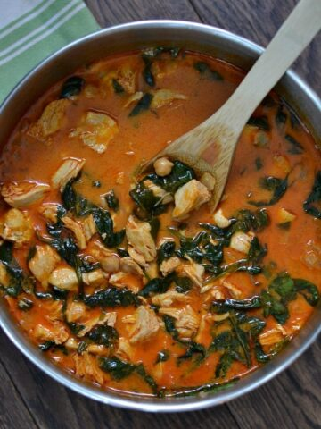 closeup of Curry Chicken and Chickpeas recipe with spinach in a stainless steel pot with wooden spoon