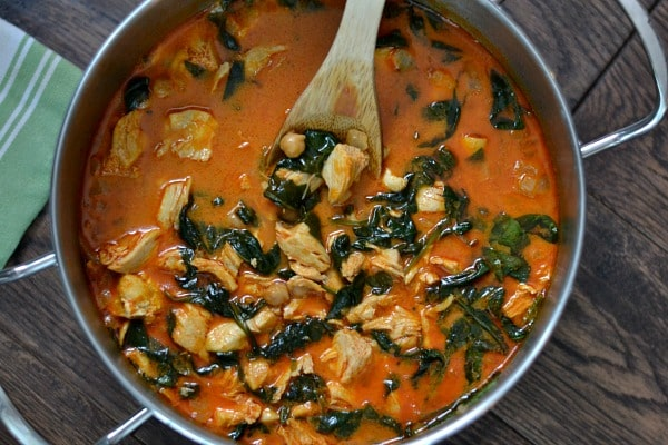 Curry Chicken and Chickpeas recipe in a pot with wooden spoon