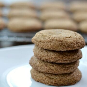 A close up of a stack of 4 molasses cookies with a cooling rack.