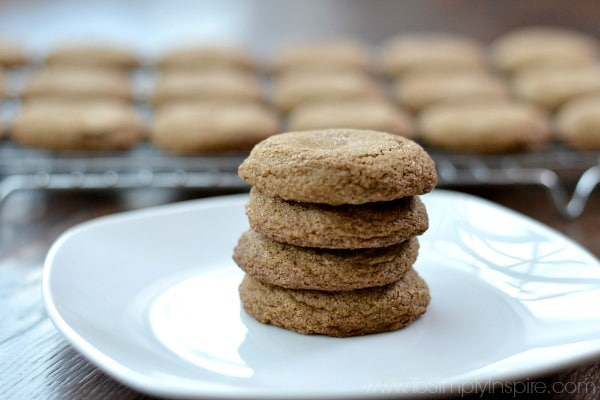 A closeup of four molasses cookies stacked on a white plate