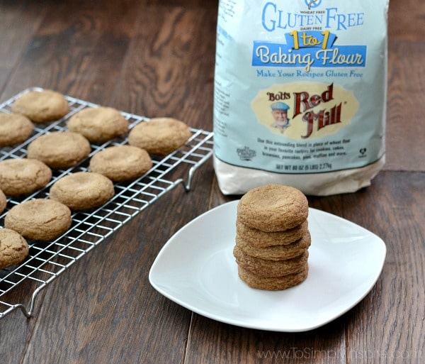 A stack of 5 molasses cookies on a white plate with a cooling rack of cookies beside and a bog of bobs red mill gluten free flour.