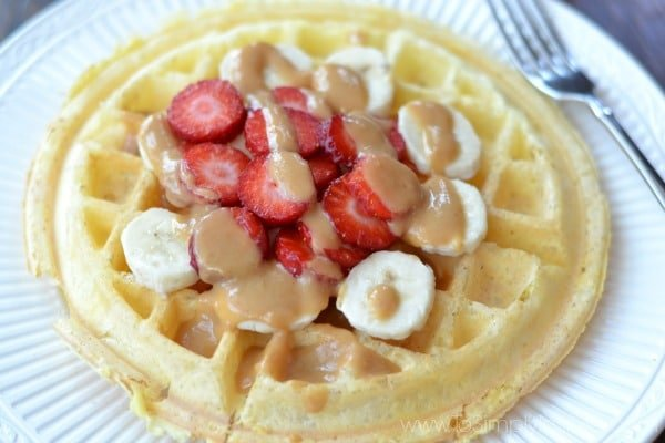 Closeup of Protein Waffle on a white plate topped with sliced strawberries and bananas drizzled with peanut butter.