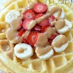 Closeup of Protein Waffle recipe topped with sliced strawberries and bananas drizzled with peanut butter.