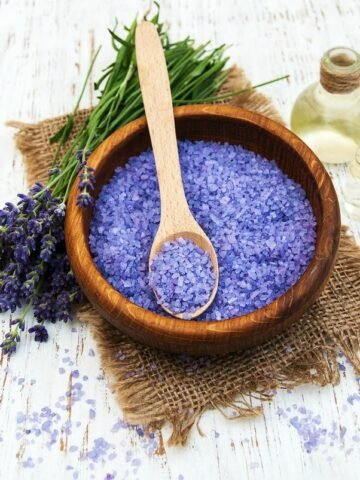 A close up of a bowl of purple bath salt in a wooden bowl with a wooden spoon