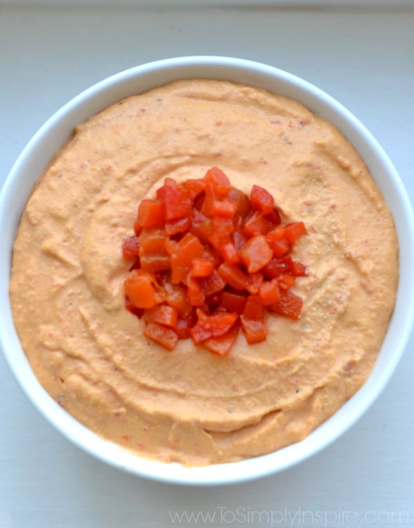A close up of Hummus topped with roasted red peppers