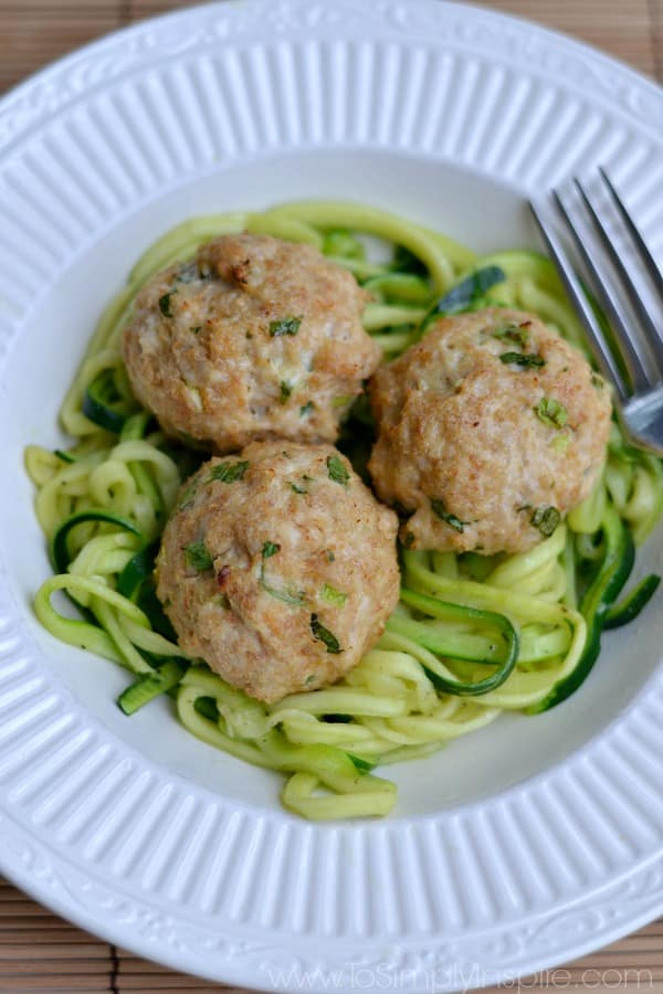 three Asian Turkey Meatballs over zucchini noodles on a white plate.