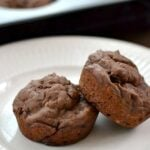 Two Chocolate banana muffins on a white plate.