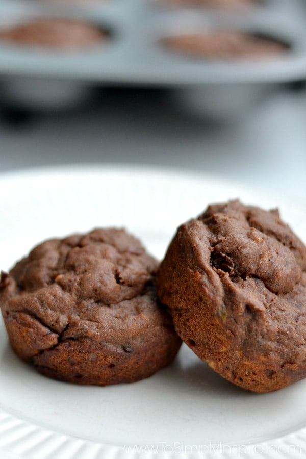 Two chocolate banana muffins recipe on a white plate.