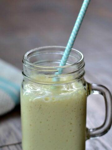A closeup of a glass mug with mango banana smoothie with a light blue straw