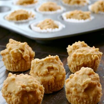 five mini carrot cake muffins on a wood table with a muffin tin in the background