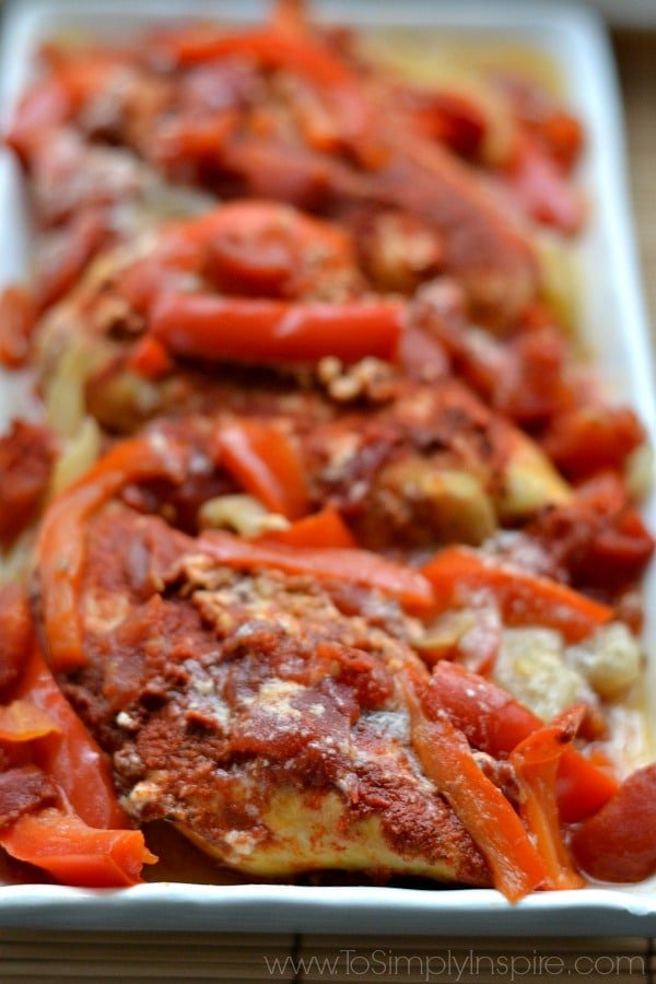 A closeup of Chicken with sliced red bell peppers and paprika