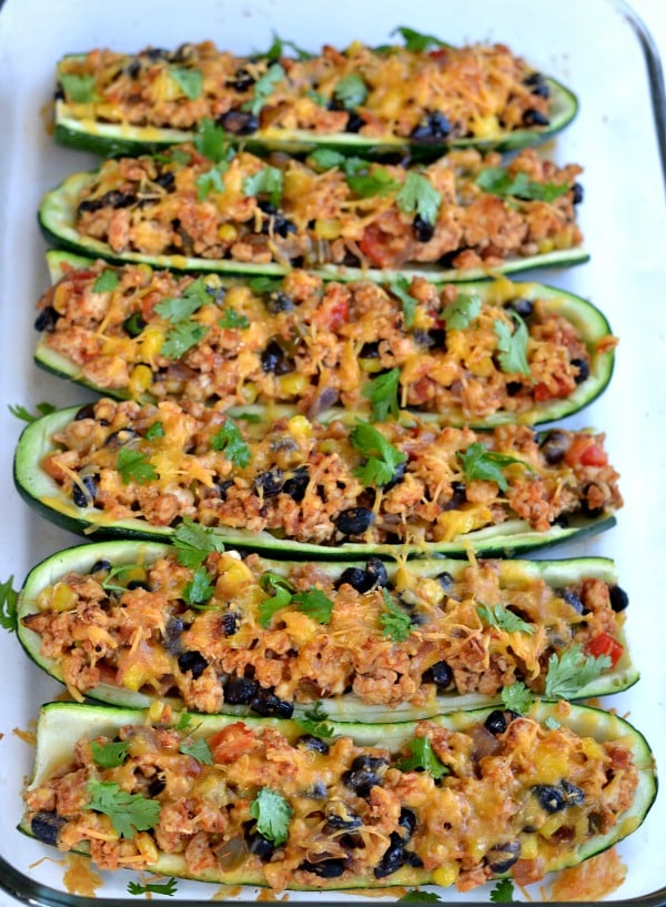 Vertical closeup of Mexican Zucchini Boats recipe with chicken, black beans and cheese and cilantro in a casserole dish