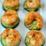 a group shrimp on top of cucumber slices