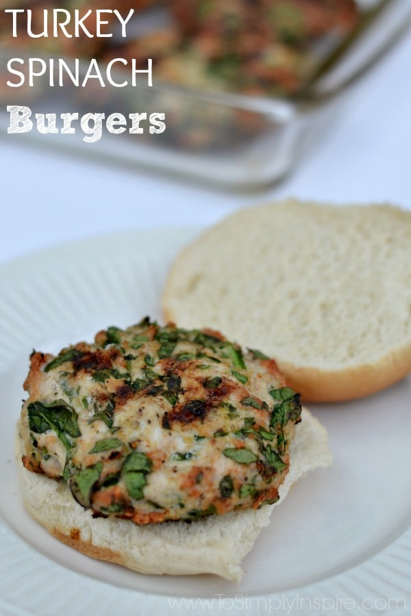 Spinach turkey burger on a open bun on a white plate