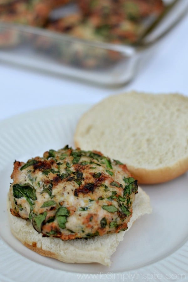 closeup of a spinach turkey burger on a white plate with an open bun