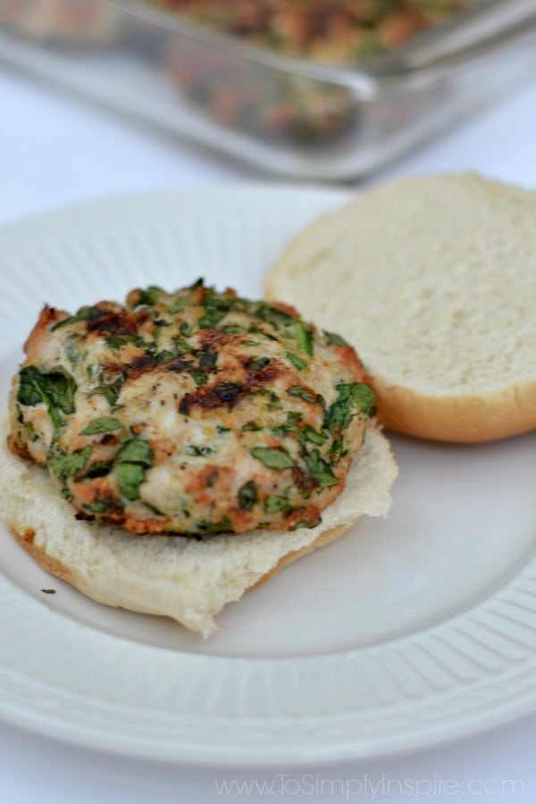 A white plate with a open spinach turkey burger