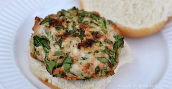 a closeup of a spinach turkey burger on a white plate