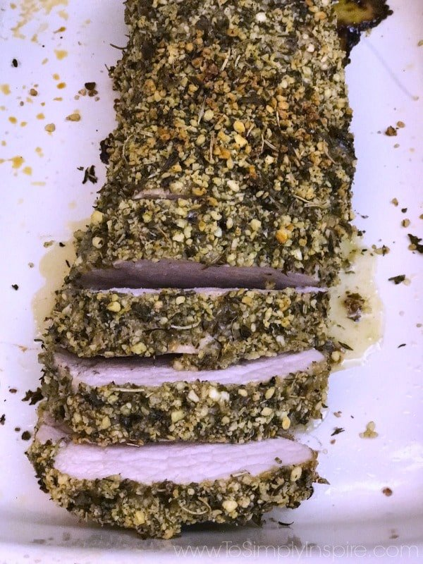 a plate with sliced Herb Crusted Pork Tenderloin topped with bread crumbs and herbs