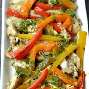 chicken with strips of red, orange and yellow bell pepper strips topped with a cilantro lime sauce