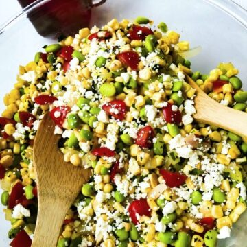 a closeup of Succotash Salad recipe in a glass bowl with two wooden serving spoons