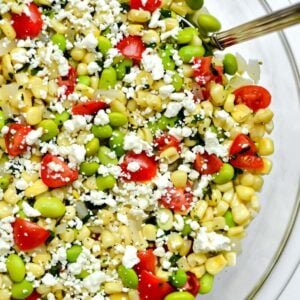 big glass bowl with succotash salad with corn kernels, lima beans and tomatoes