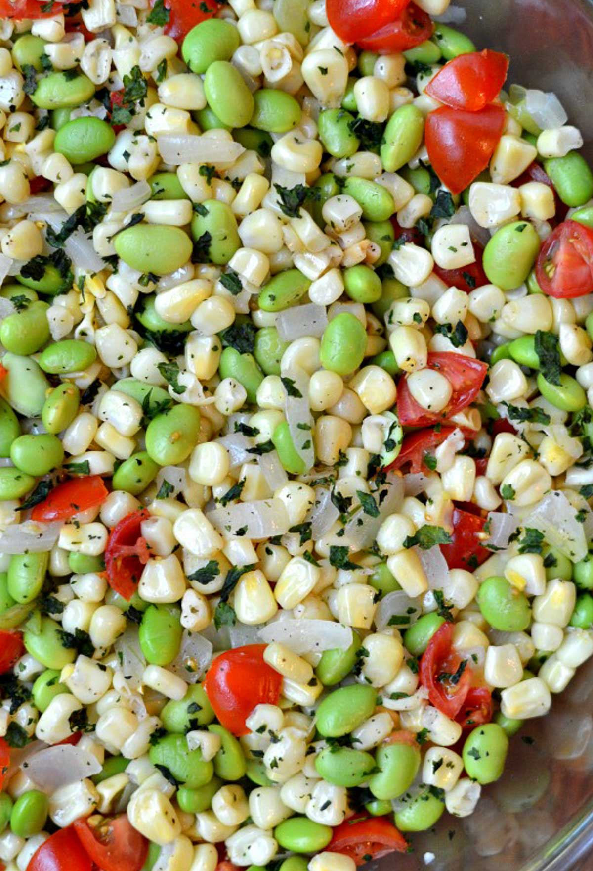a mixture of corn kernels, butter beans and tomatoes in a big bowl
