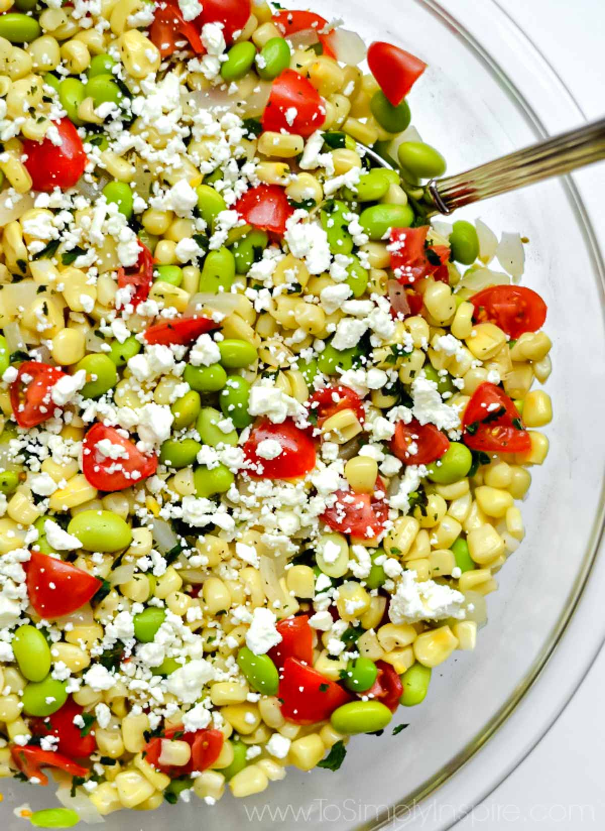succotash salad with corn kernels, lima beans and tomatoes in a big glass bowl with a spoon